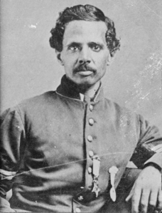 His name: Sgt. Powhatan Beaty. His photo from the Library of Congress, donated by W.E.B. DuBois, after it was put on display for an exhibition Paris. His Medal of Honor was earned at Chaffin's Farm (AKA Chapin's Farm) (AKA New Market Heights), a 2-day engagement, day 1: conquest of Richmond, decapitating the South; day 2: repulsing a rebel counter-attack (reminiscent of the Battle of the Bulge). We held firm. Lincoln was there as described, at the front the next day (a frequent target not only when visiting the front, but also in DC, his appearance being quite distinctive, even at a distance), having waited on board a ship with a stateroom built quickly by the ship's crew especially for him, because of his remarkable height (and sleeping length!). Sgt. Beaty's injuries included an eye injury (blinded by splinters from shelling of wooden fortifications, similar to injuries suffered by sailors from artillery damage to war-ships in battle), and later in the battle, a skull fracture. After all the officers were cut down, & an 80% casualty rate in his company(!), which pulled back with their wounded, not leaving wounded in the field of battle, he took charge, personally charging up-hill 600 yards (!!!) -- with extra-ordinary valor -- to retrieve the fallen flag, dropped earlier when the color-bearer (a common target) was shot down, leading what was left of the company back into battle, to take the hill, and hold it until relieved. The President of the United States of America, in the name of Congress, takes pleasure in presenting the Medal of Honor to First Sergeant Powhatan Beaty, United States Army, for extraordinary heroism on 29 September 1864, while serving with Company G, 5th Colored Infantry, in action at Chapin's Farm, Virginia. First Sergeant Beaty took command of his company, all the officers having been killed or wounded, and gallantly led it. The man who fought with mangled arm amputated on the field of battle & led his men at the top of the hill was Corporal Miles James; he was one of a dozen other men (all African American) who also received the highest military honor for their actions that day: the Congressional Medal of Honor, Awarded personally by the President of the United States (Cpl James survived the actions that day, and was alive to receive it from the grateful President of the United States. Noted by Chris Tiffany